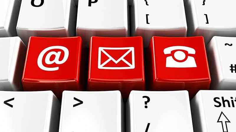 Detalle de Teclado con teclas destacadas en rojo con iconos de @, mail y teléfono